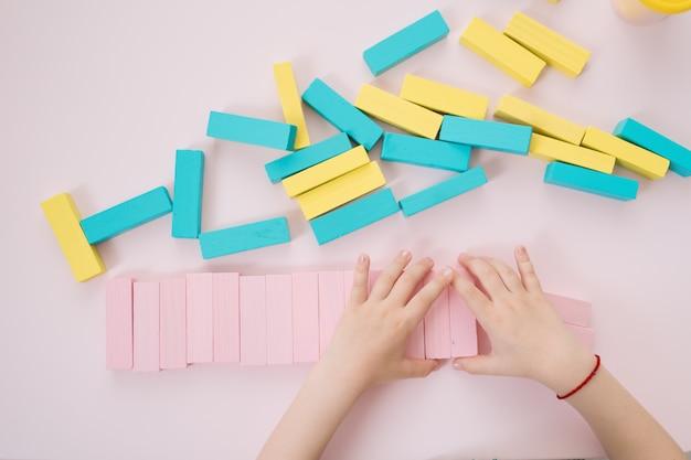 Belas garotas caucasianas, brincar com os blocos multicoloridos de madeira