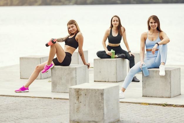Belas garotas treinando. meninas de esportes em um sportswear. mulheres perto da água.