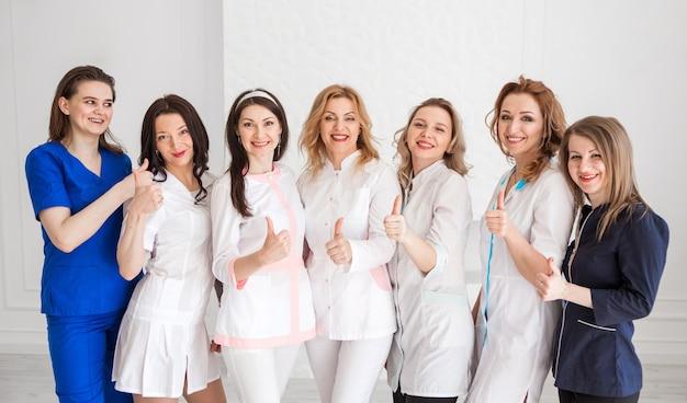 Belas jovens médicas em uniformes brancos posando no contexto de uma parede branca, mostrando a classe com a mão e olhar para a câmera e sorrisos.