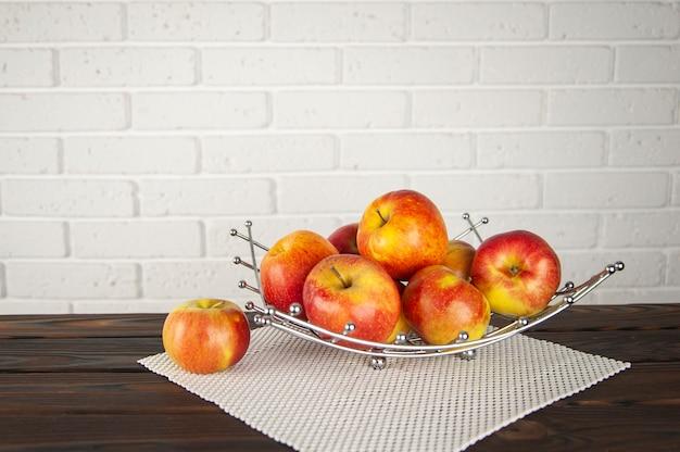 Belas maçãs em uma fruteira em uma superfície de madeira
