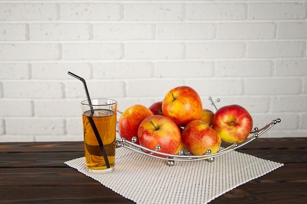 Belas maçãs em uma fruteira sobre uma superfície de madeira e um copo de suco de maçã