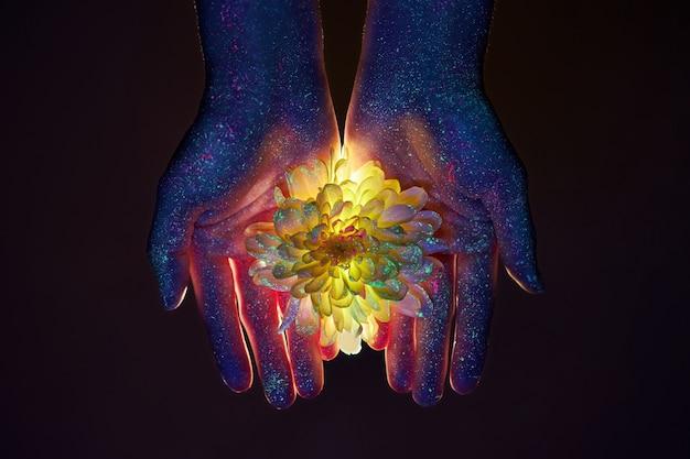 Belas mãos de uma mulher em luz ultravioleta com flores nas palmas