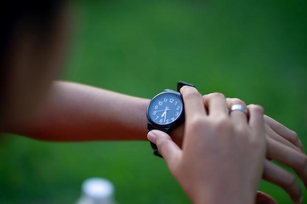 Belas mãos e relógios pretos uma verificação de tempo para precisão e pontualidade