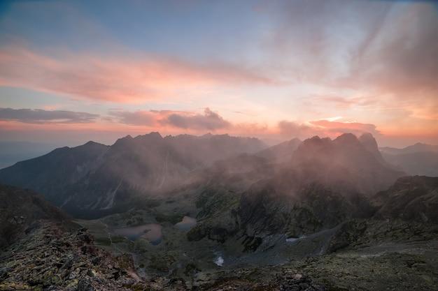 Belas montanhas ao pôr do sol com nuvens cor de rosa e um lago na paisagem do vale