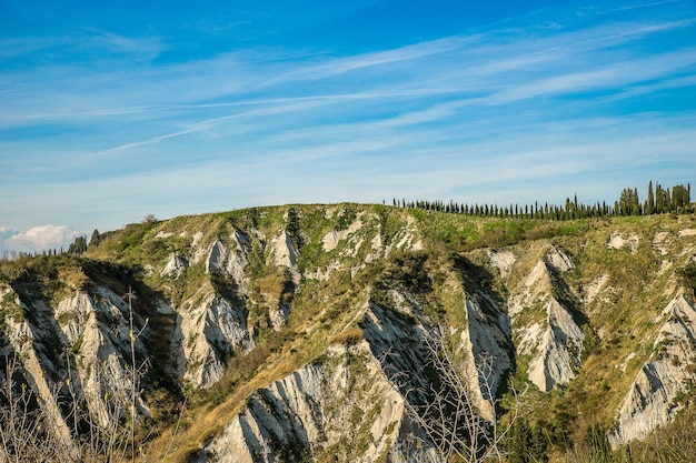 Belas montanhas cobertas de árvores e grama sob as incríveis nuvens no céu