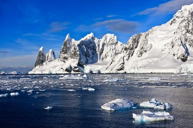 Belas montanhas cobertas de neve contra o céu azul na antártida