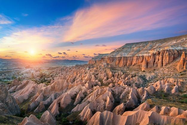 Belas montanhas e vale vermelho ao pôr do sol em goreme, capadócia, na turquia.