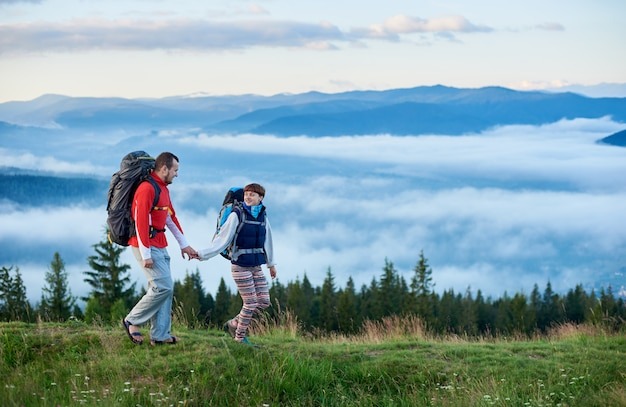 Belas montanhas na névoa da manhã e um jovem casal andando na trilha verde com mochilas