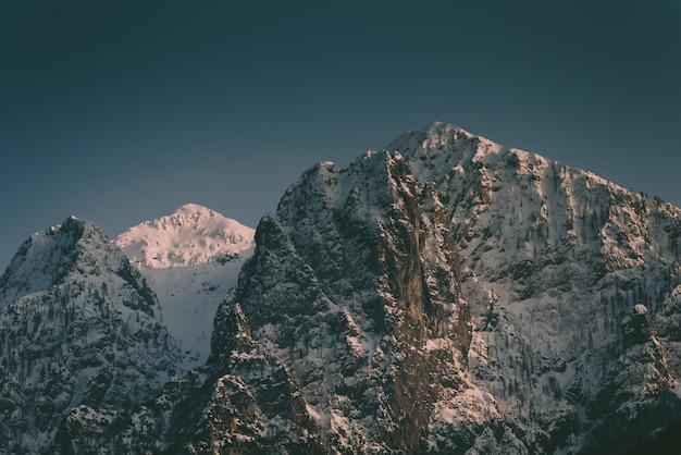 Belas montanhas rochosas altas com uma montanha de neve no meio