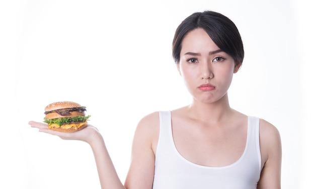 Belas mulheres asiáticas comendo hambúrguer isolado. comida rápida