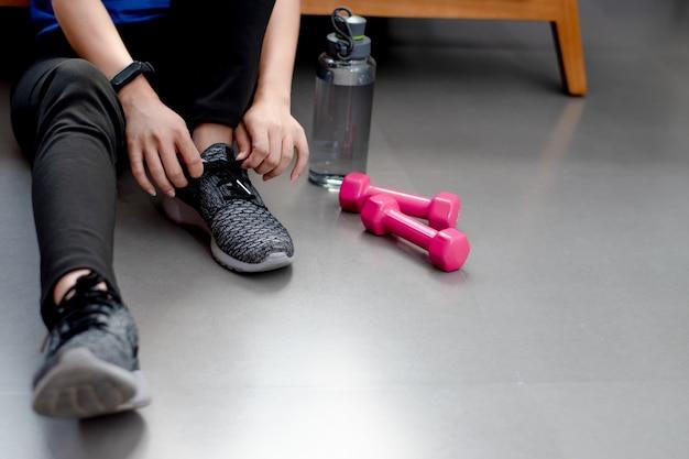 Belas mulheres asiáticas estão amarradas aos sapatos. ela está se exercitando em casa.
