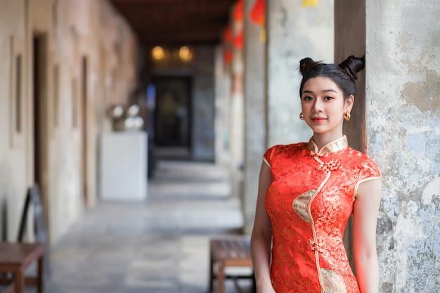 Belas mulheres asiáticas estão sorrindo. ela usava um cheongsam chinês vermelho.