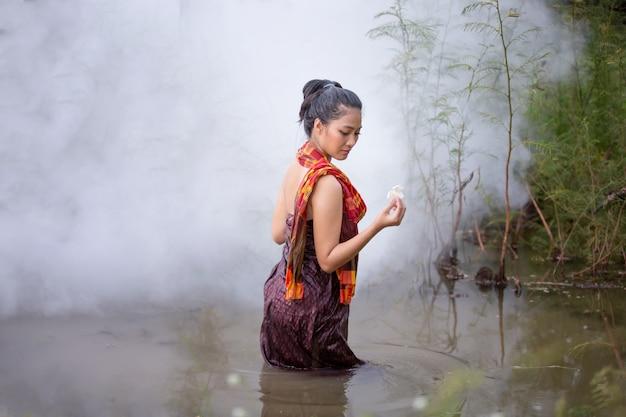 Belas mulheres asiáticas estão tomando banho no rio.