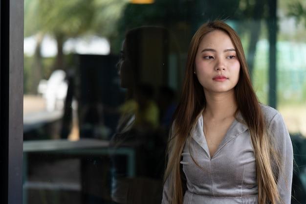 Belas mulheres asiáticas, mulheres que trabalham, em pé na frente do escritório