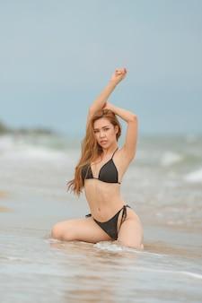 Belas mulheres asiáticas ou tailandesas e biquínis pretos na praia, relaxando na praia para viajar no conceito de verão