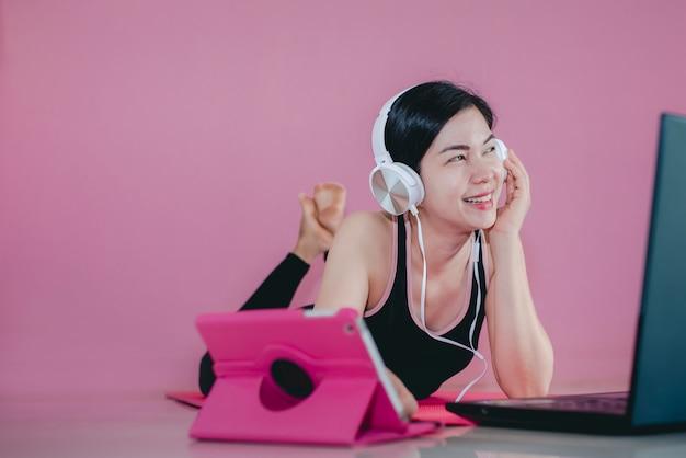Belas mulheres asiáticas usam fones de ouvido, exercitam roupas esportivas pretas, deitam-se, assistem a vídeos de exercícios em casa e notebooks.