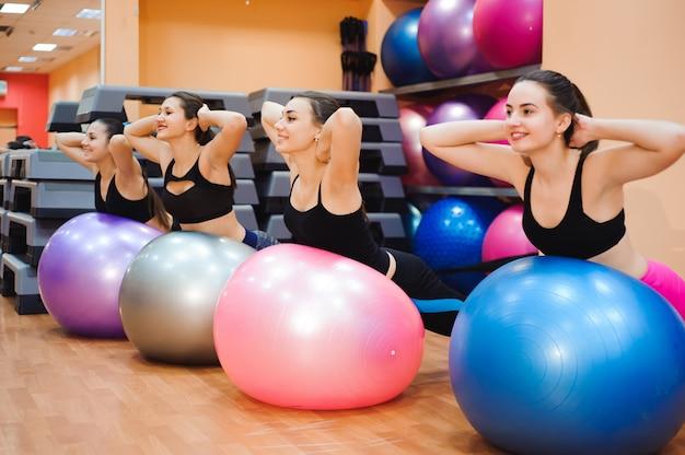 Belas mulheres caucasianas fazendo exercício com bola de ginástica