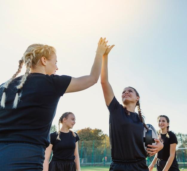 Belas mulheres esportivas levantando as mãos