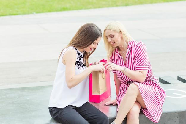 Belas mulheres jovens com as amigas olhando no saco de compras