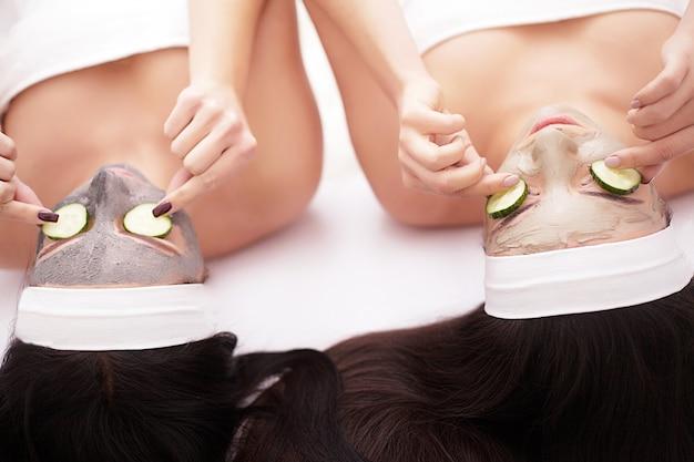 Belas mulheres jovens segurando pedaços de pepino em seus olhos e sorrindo enquanto na cama