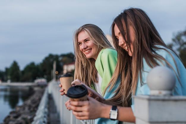 Belas mulheres segurando copos de café