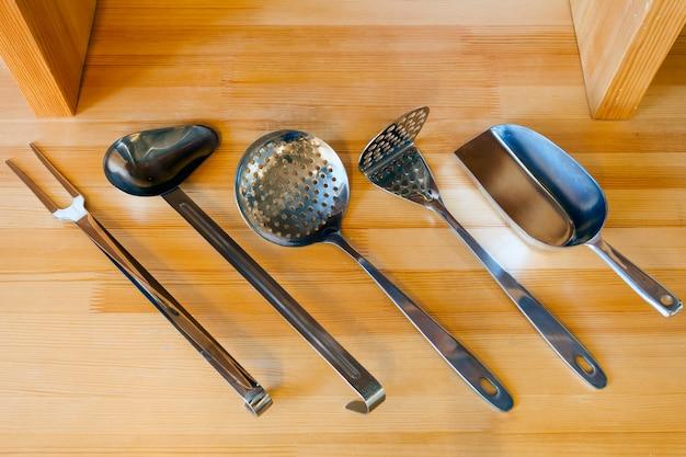 Belas novas ferramentas de cozinha em uma mesa de madeira
