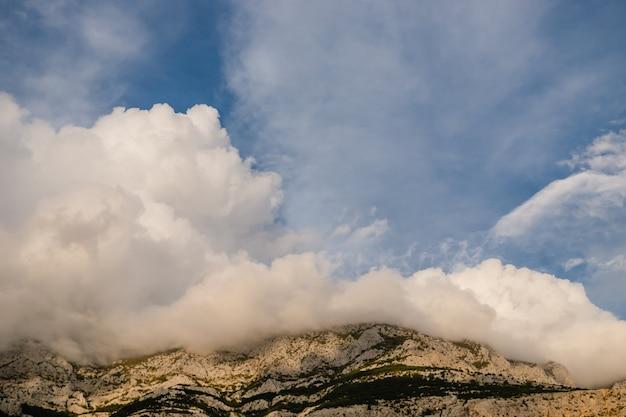 Belas nuvens baixas caem nas montanhas em brela, croácia