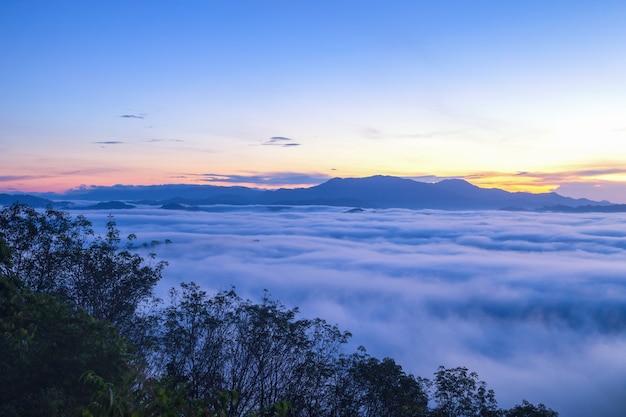 Belas nuvens fluindo e a névoa em frente às montanhas de khao khai nui no nascer do sol, província de phang-nga, tailândia