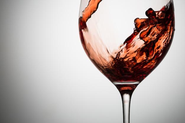 Belas ondas de vinho tinto em closeup de vidro