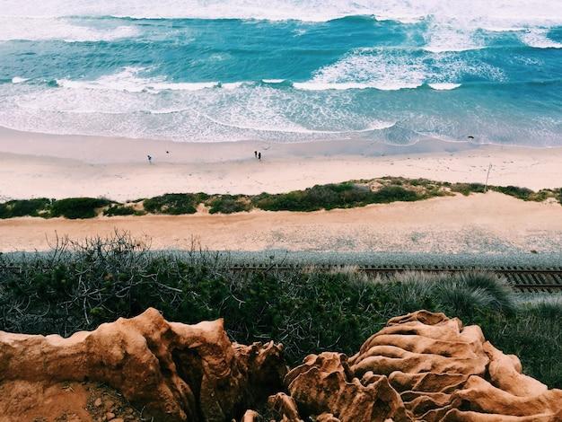 Belas paisagens da praia com poucas pessoas atiradas de um terreno mais alto