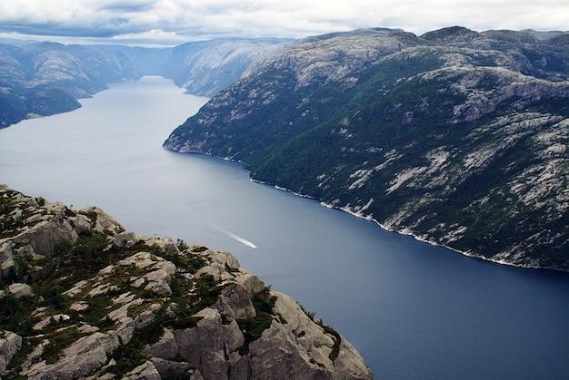 Belas paisagens das famosas falésias de preikestolen perto de um lago sob um céu nublado em stavanger