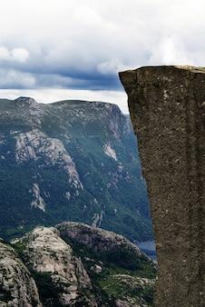 Belas paisagens das famosas falésias preikestolen perto de um lago sob um céu nublado em stavanger, noruega