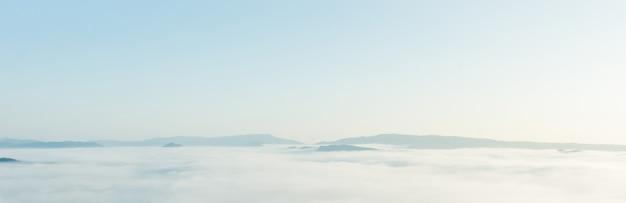 Belas paisagens das montanhas com branco nevoento pela manhã.