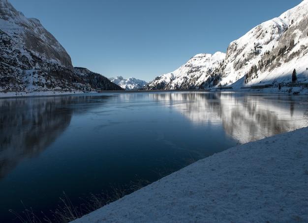Belas paisagens de altas montanhas cobertas de neve refletindo no lago nas dolomitas