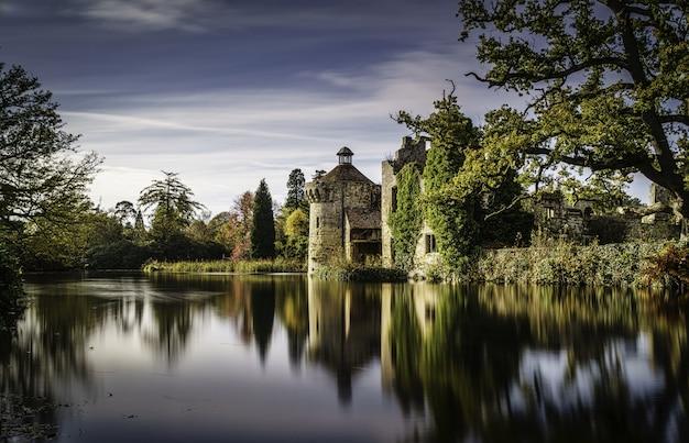 Belas paisagens de um castelo refletindo no lago claro, cercado por diferentes tipos de plantas