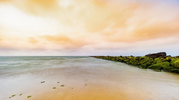 Belas paisagens de um mar sob um céu nublado durante um belo pôr do sol, rodeado por vegetação