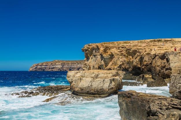 Belas paisagens de um penhasco rochoso perto das ondas do mar sob o lindo céu azul