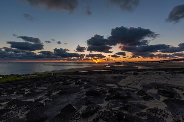 Belas paisagens de um pôr do sol de tirar o fôlego sobre o oceano calmo em westkapelle, zelândia