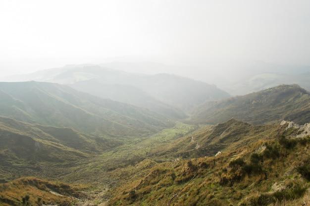 Belas paisagens de uma cadeia de montanhas verdes envoltas em névoa