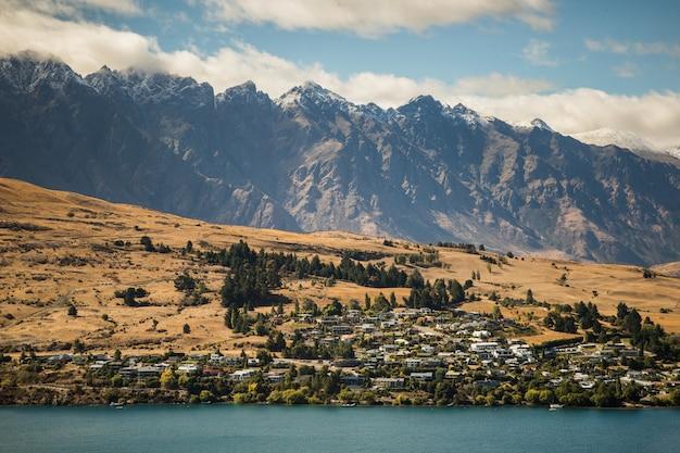 Belas paisagens de uma paisagem com muitos edifícios perto de altas montanhas rochosas à beira-mar