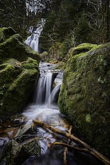 Belas paisagens de uma poderosa cachoeira em uma floresta perto de formações rochosas cobertas de musgo