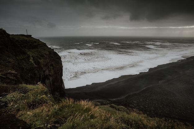 Belas paisagens do mar cercado por formações rochosas envoltas em névoa na islândia