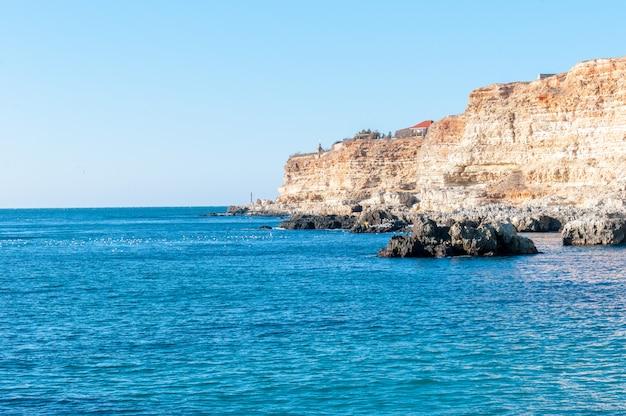 Belas paisagens do mar negro no sul da rússia. orange mountains e muitos pássaros nas rochas da praia