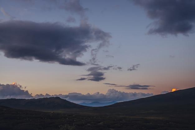 Belas paisagens montanhosas com luz dourada do amanhecer no céu nublado. cênica paisagem montanhosa com cores iluminantes no céu do sol. silhuetas de montanhas ao nascer do sol. ouro iluminando a luz do sol no céu