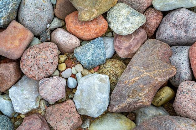 Belas pequenas pedras do mar. close-up de seixos coloridos multicoloridos em uma praia.