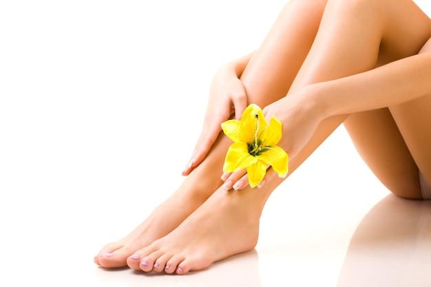 Belas pernas bem cuidadas de menina com uma flor amarela na mão em um fundo branco