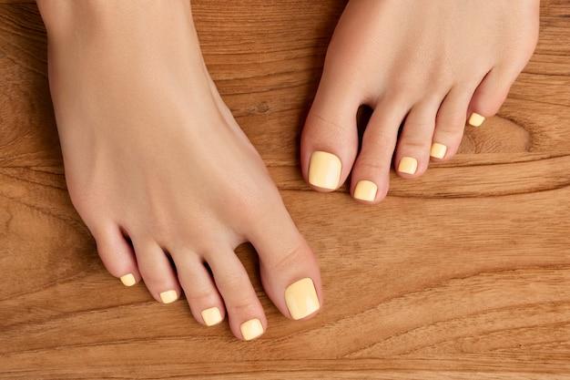 Belas pernas de mulher com desenho de unhas de verão na superfície de madeira