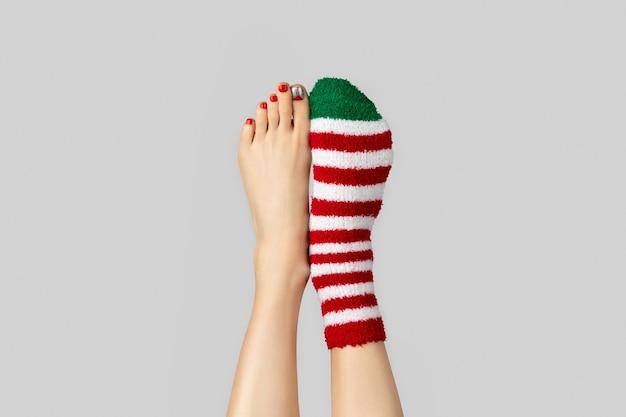 Belas pernas de mulher com design de unhas de natal e meias