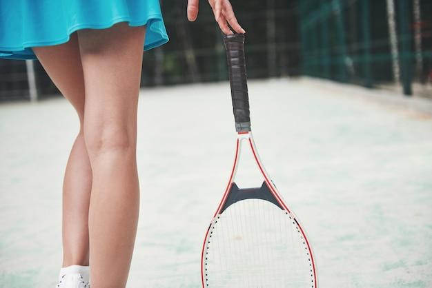 Belas pernas de tênis na quadra com uma raquete.