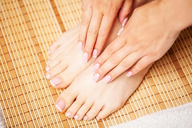 Belas pernas de uma mulher com uma pedicure francesa fresca